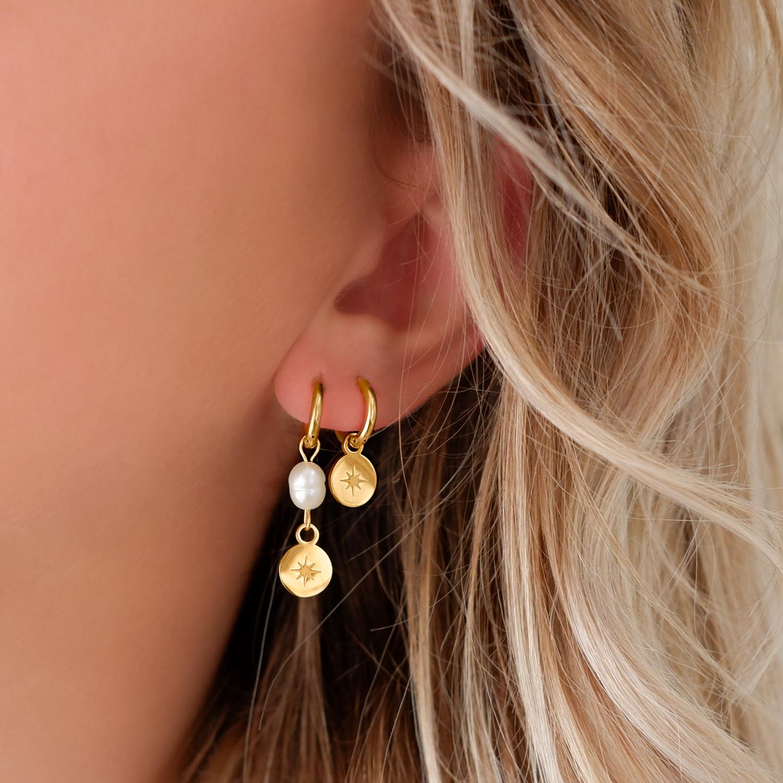 Vrouw draagt gouden parel oorbellen in oor
