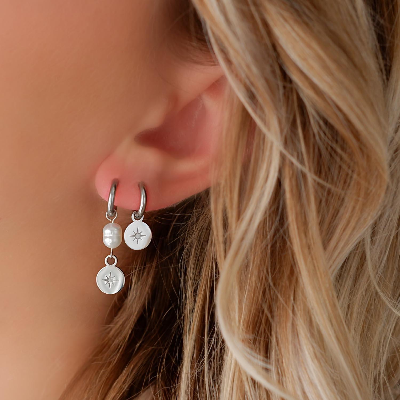 Vrouw draagt zilveren parel oorbellen in oor