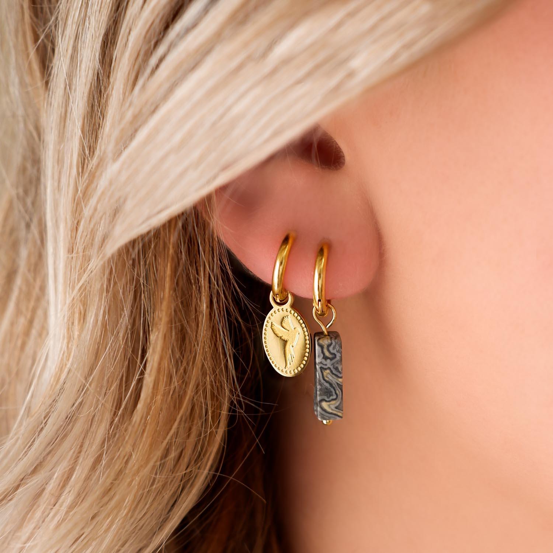 Trendy oorbellen met steen in het oor voor een trendy look