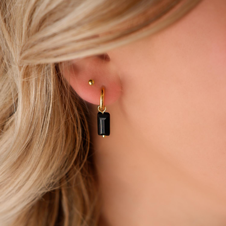 gouden stud oorbellen in het oor voor een trend look