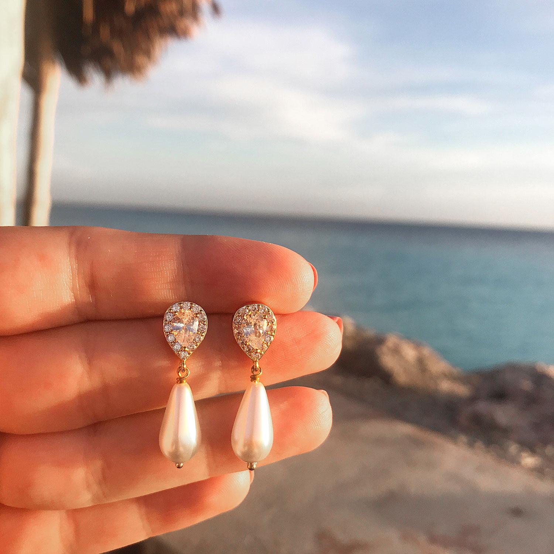 Mooie faux pearl oorbellen in de hand op een zonnige bestemming