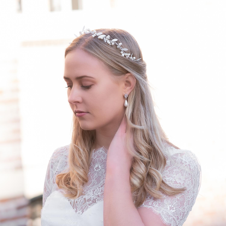 Bruid draagt mooie faux pearl oorbellen in het oor voor complete look