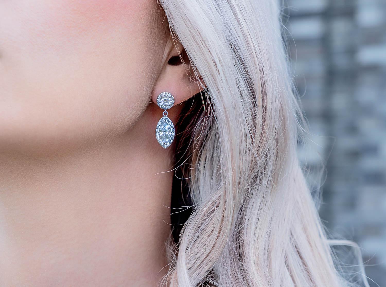 Blonde vrouw draagt luxe oorbellen met sparkle hanger