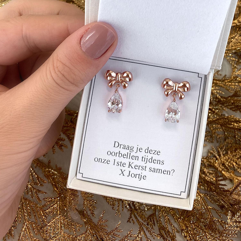 hangende rose gouden oorbellen met strikje en kristal in doosje met tekst