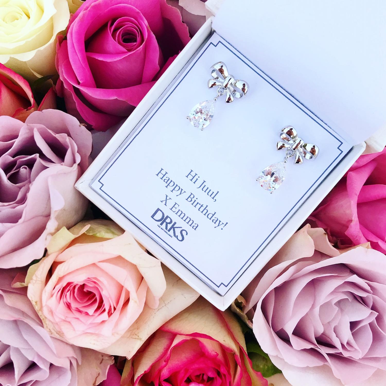 Zilveren bow oorbellen in een sieradendoosje met rozen