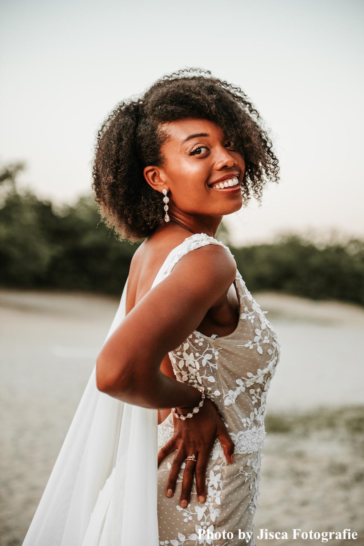 Bruid draagt rose gouden bruidsarmband en oorbellen