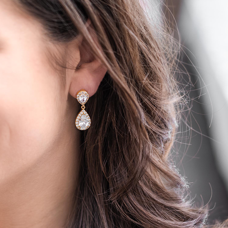 Vrouw met donkere haren draagt daily luxury oorbellen in het oor