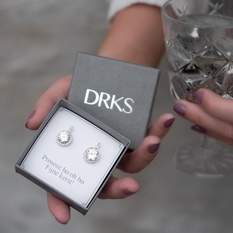 Vrouw geeft een sieradendoosje met mooie oorbellen in een doosje
