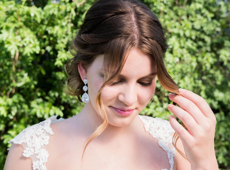 bruid met bruidskapsel en grote oorbellen van drks