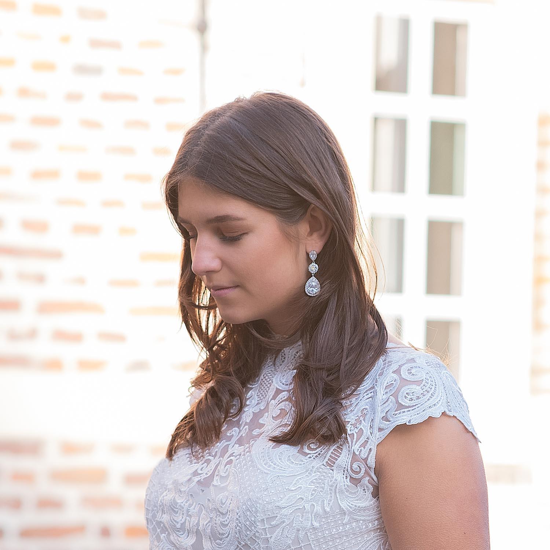 Bruid draagt mooie bruidsoorbellen in het oor voor een complete bruidslook