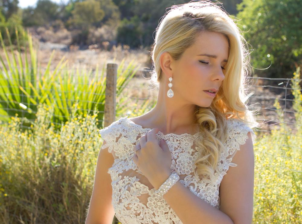 Vrouw draagt zilveren oorbellen in het oor voor een complete trouwlook