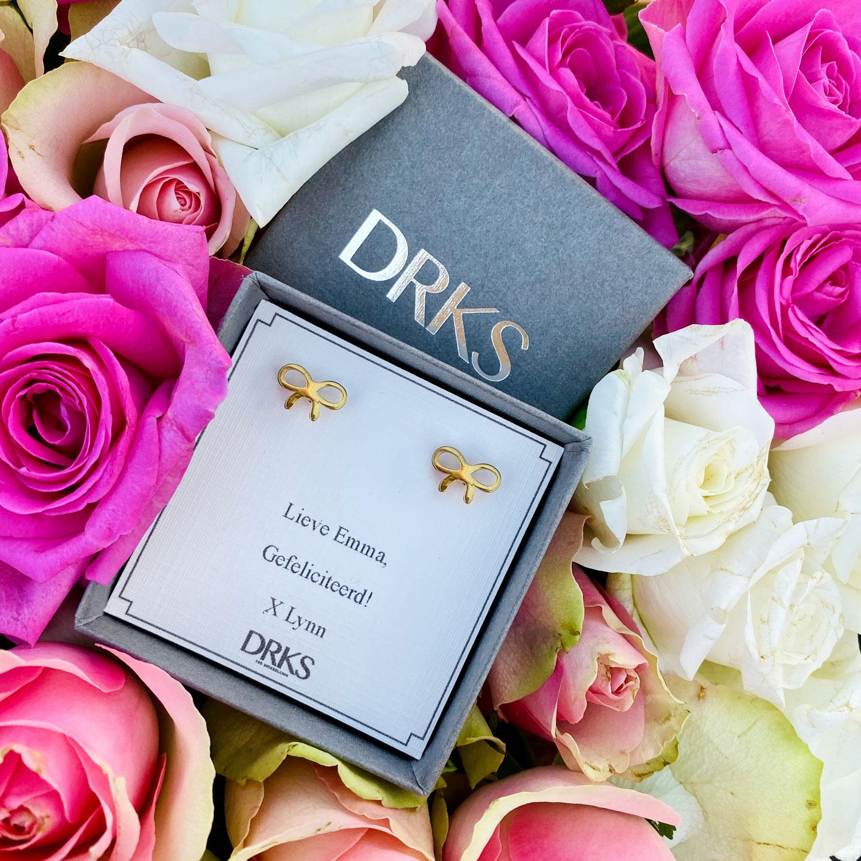 Leuke gouden oorbellen met een strikje in een sieradendoosje