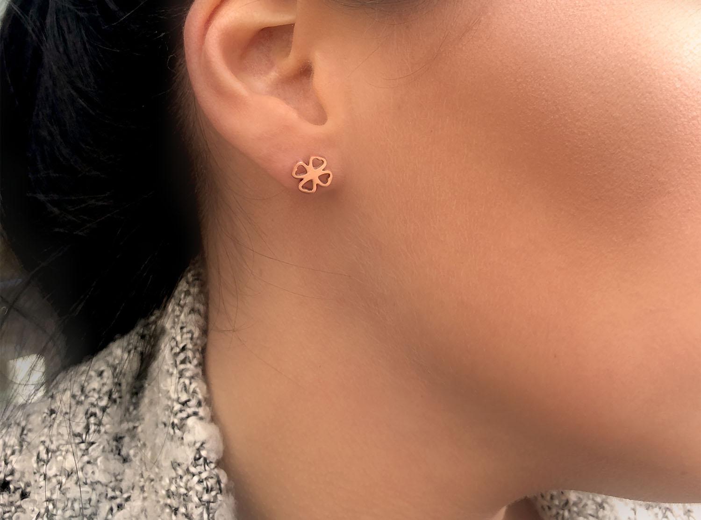 Vrouw draagt rose gouden klaver oorbellen in oor