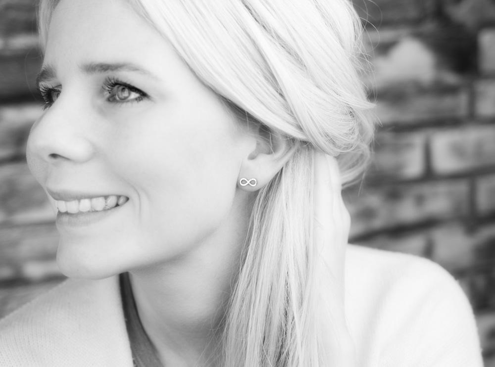 Vrouw draagt zilveren oorbellen met infinity teken