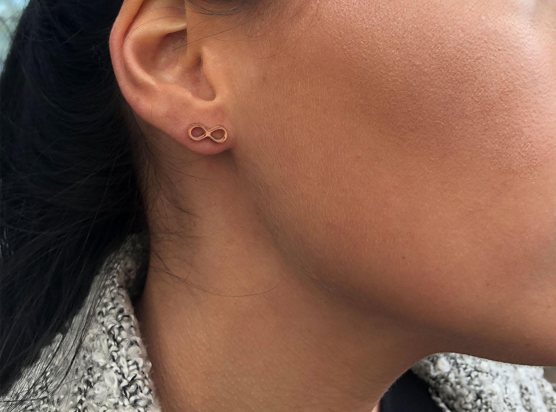 vrouw draagt rose gouden infinity oorbellen