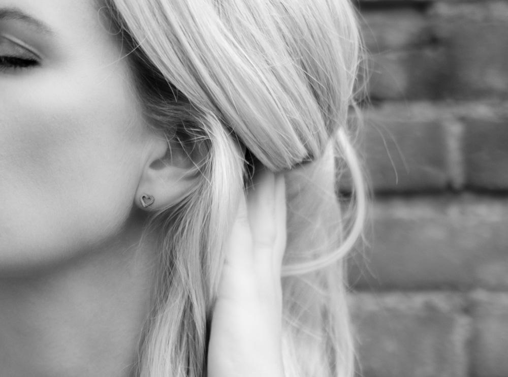 Zilveren hartjes oorbellen bij vrouw met blond haar