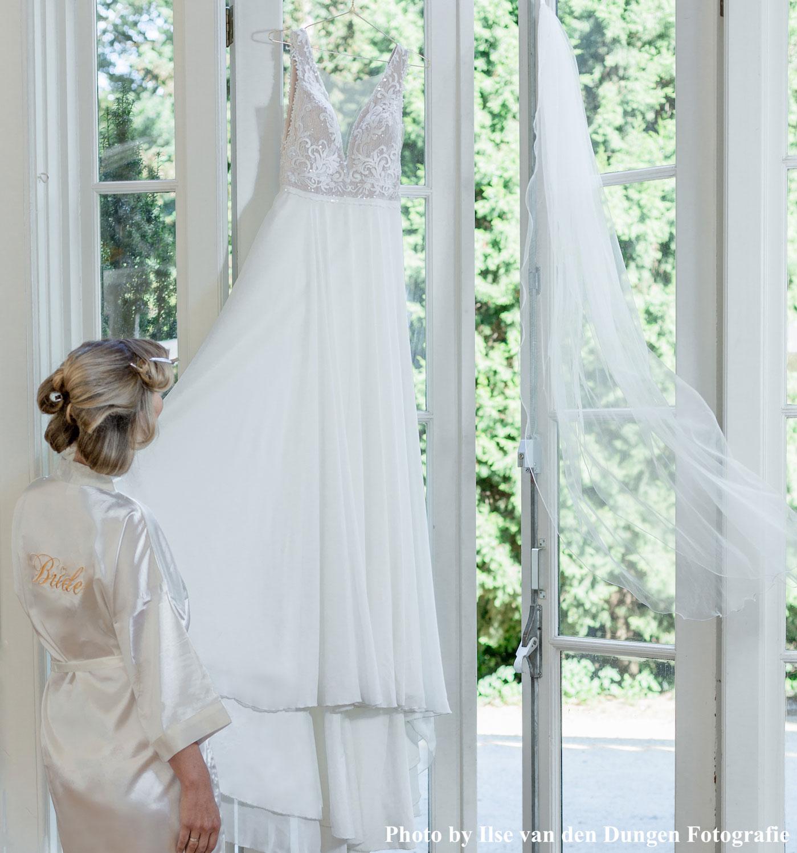 Bruid in witte drks kimono kijkt naar bruidsjurk