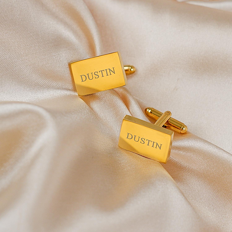 Gouden manchetknopen met naam op satijn