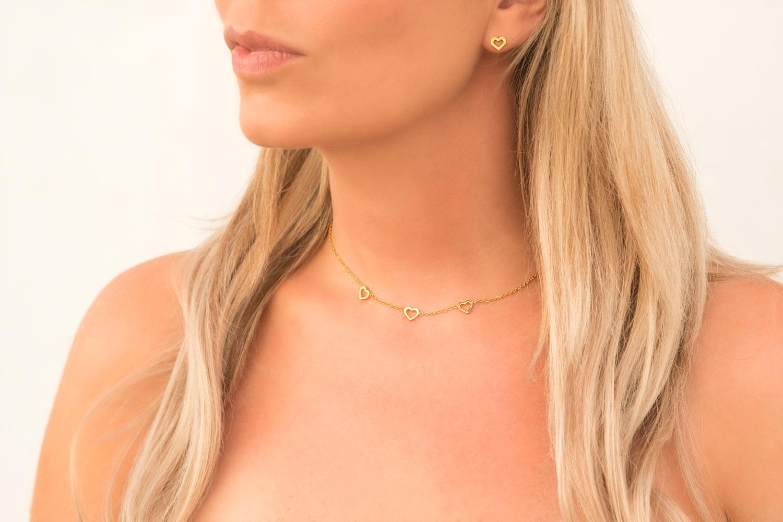 Gouden ketting met hartjes om de hals samen met hartjes oorbellen