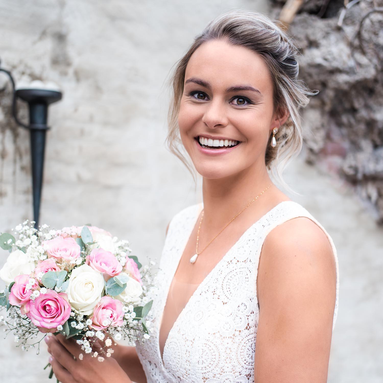 Bruid draagt een mooie set van oorbellen en ketting met een parel eraan