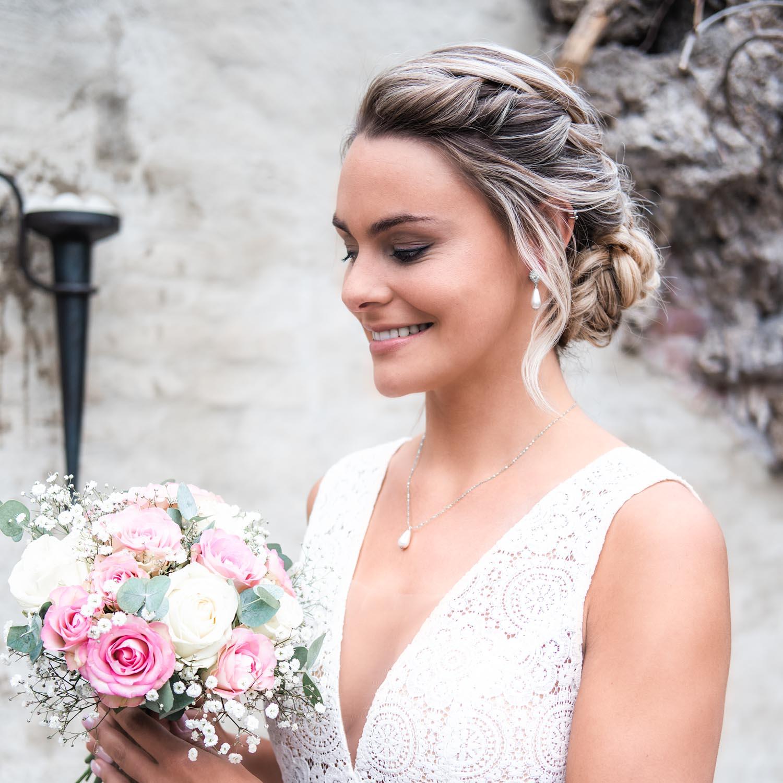 Vrouw draagt parelketting met oorbellen in het oor voor een complete look