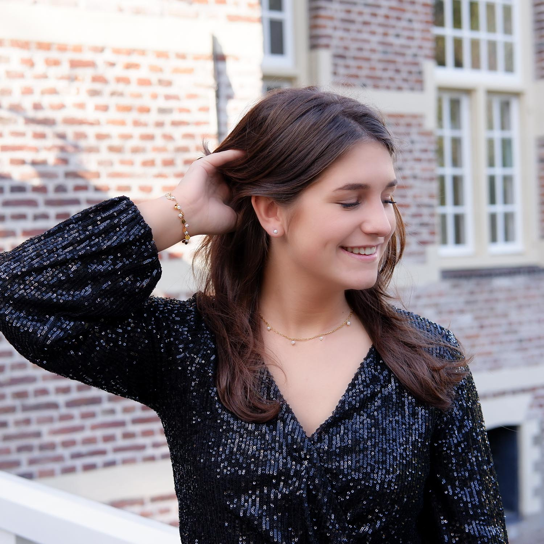Vrouw draagt een mooie set van parel oorbellen kettingen en armband