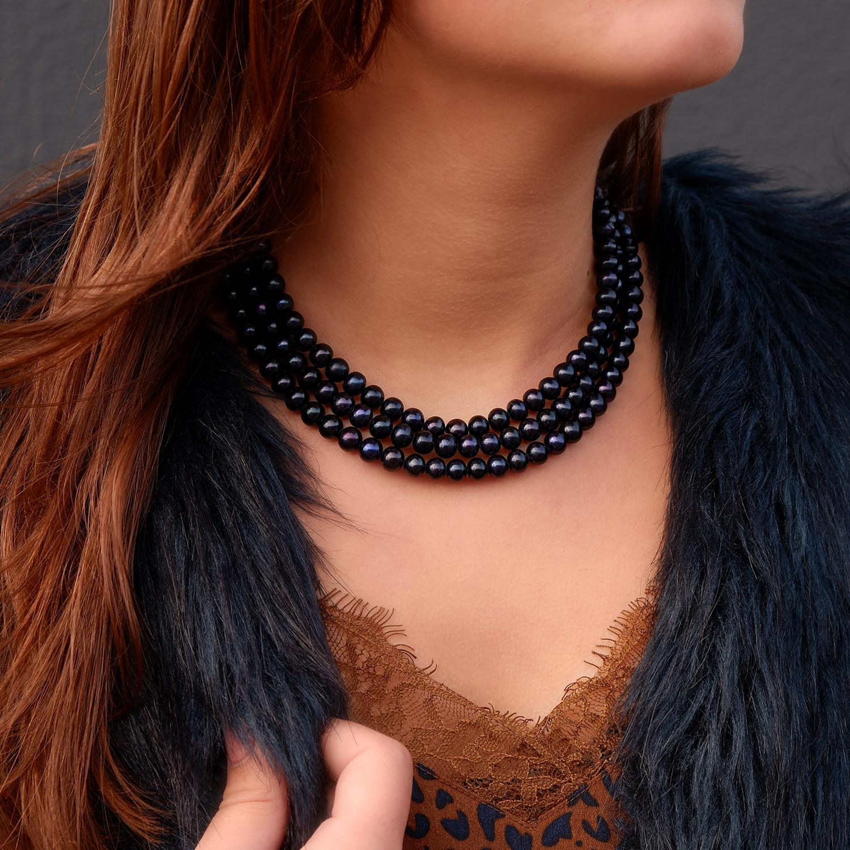 Prachtige donkerblauwe parelketting om de hals voor een feestje