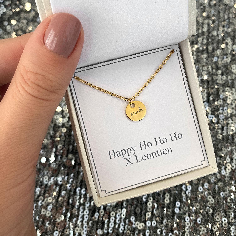 Gouden ketting met een muntje en een naam in een sieradendoosje