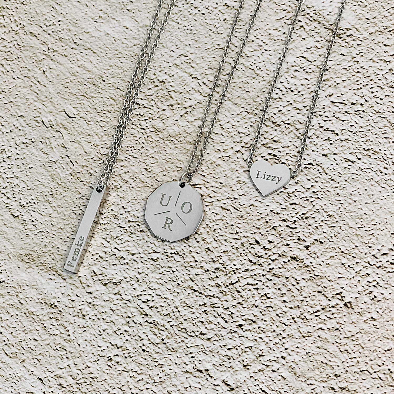 Zilveren kettingen op stenen ondergrond met gravering