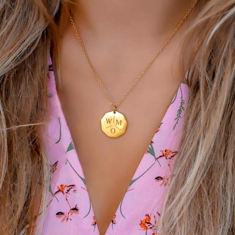 ketting met drie letters om de hals bij een roze jurk