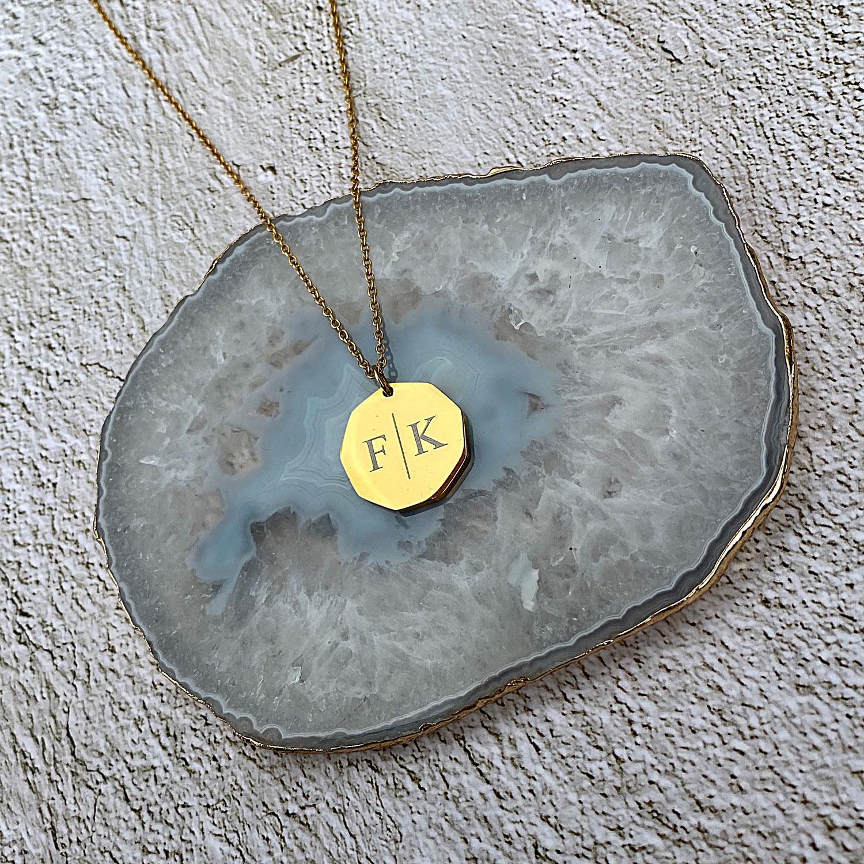 Gouden ketting met twee letters op stenen ondergrond
