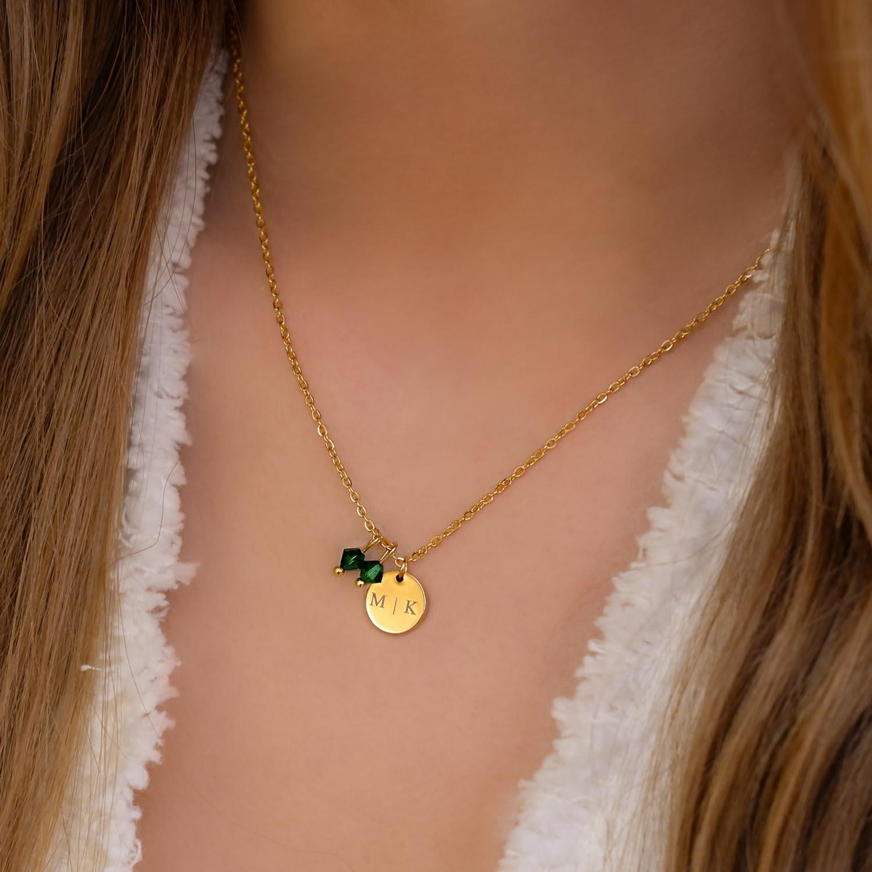Goud kleurige birthstone kettingen bij vrouw om hals