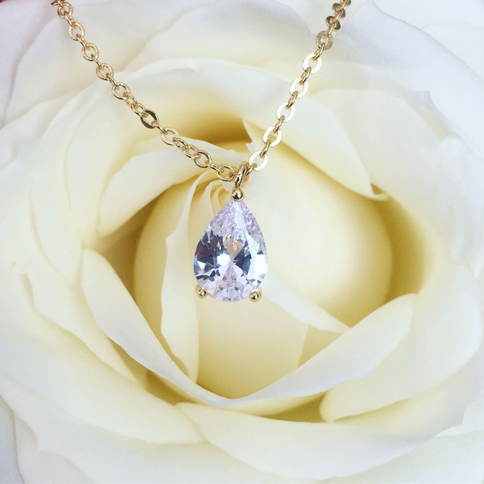 gouden ketting met steen samen met mooie rozen