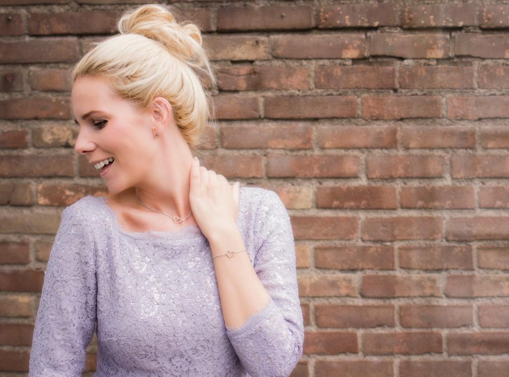 Vrouw draagt zilveren hartjes sieraden met paarse jurk