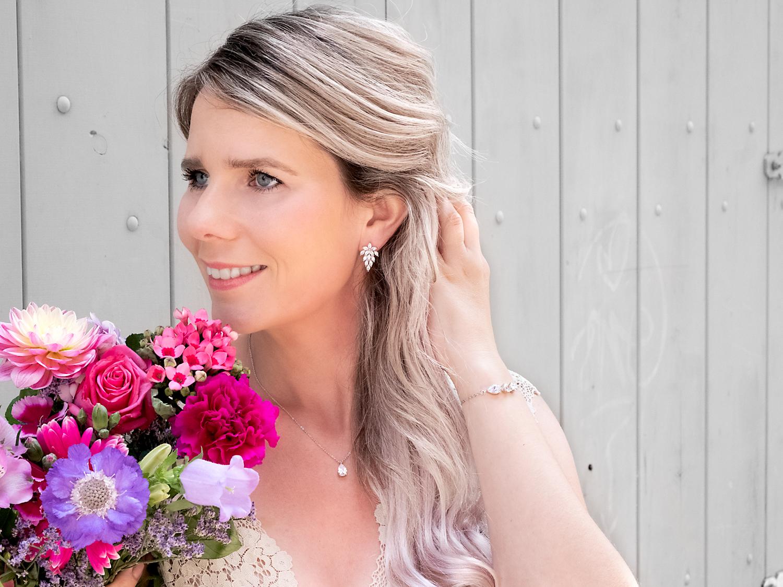 Vrouw draagt een zilveren sieradenset voor haar bruiloft met bloemen