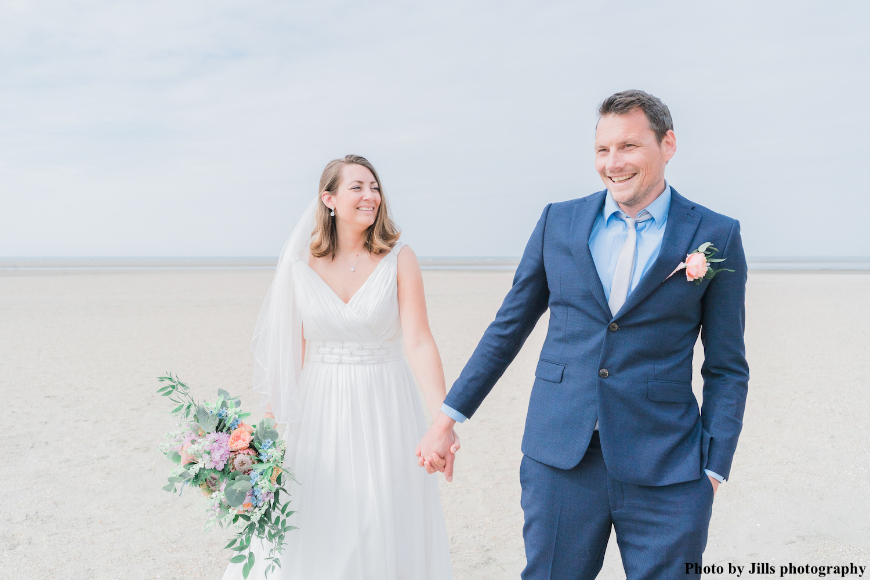 bruid met drks sieraden samen met bruidegom op het strand