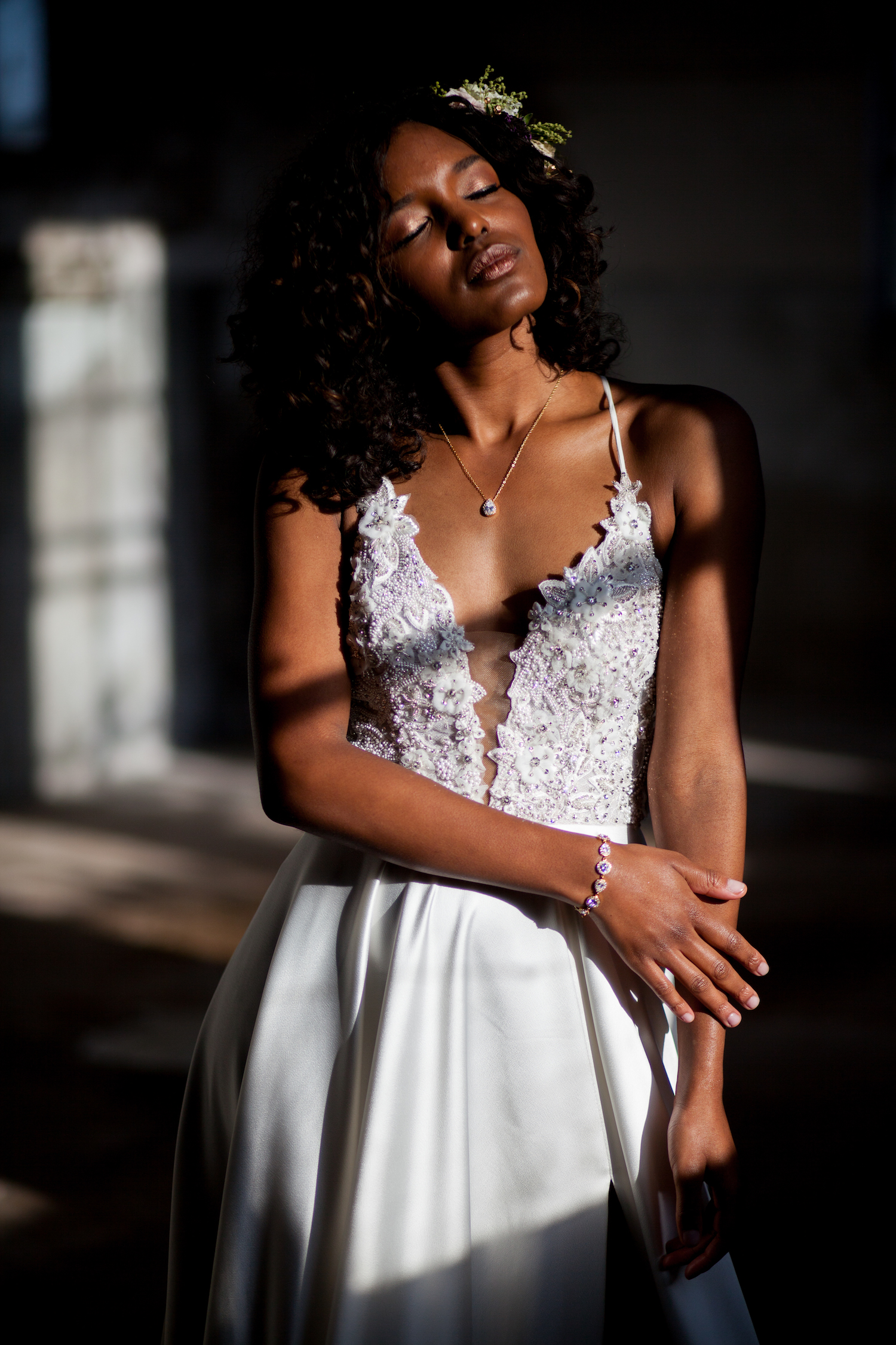 Bruid met donker haar in zonlicht met rose gouden sieraden om