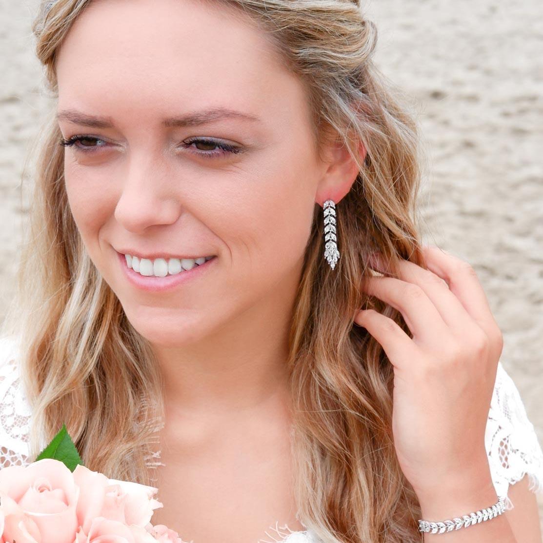 bruid met zilveren bruids oorbellen en boeket