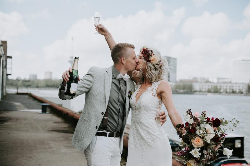 Bruidspaar met champagne bij kade