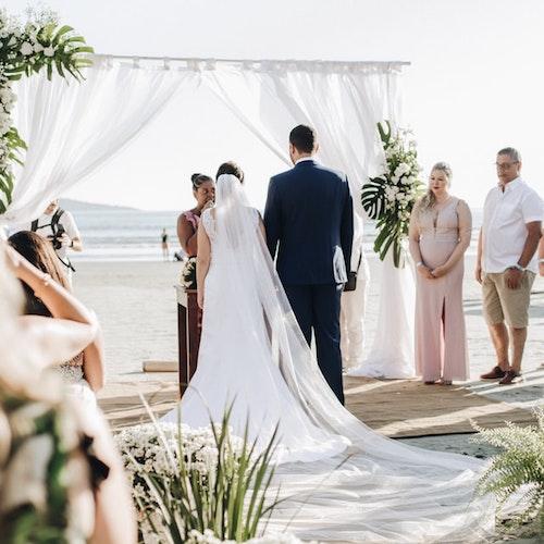 Bohemian bruiloft op het strand met bruidskoppel en gasten
