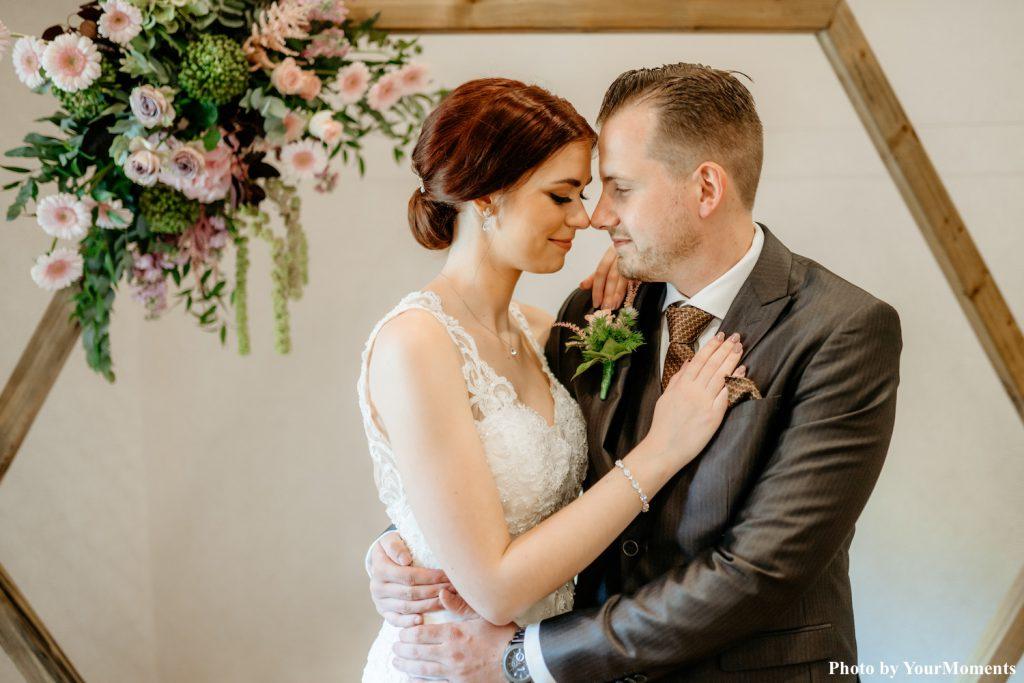 bruidspaar met zilveren bruidssieraden en bloemen