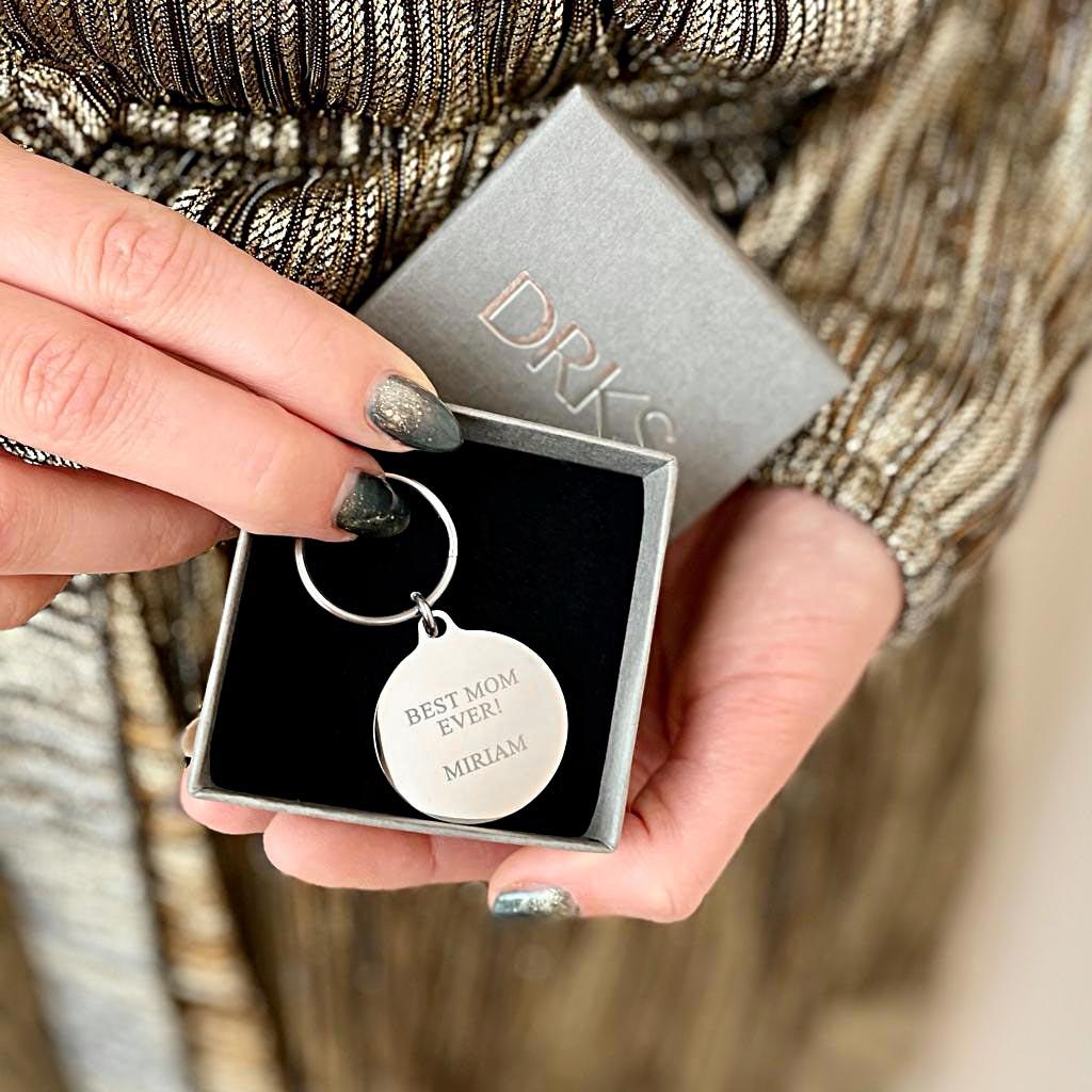 zilveren sleutelhanger rond met gravering in doosje