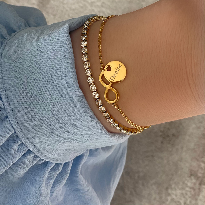 gouden armparty met gravering om pols