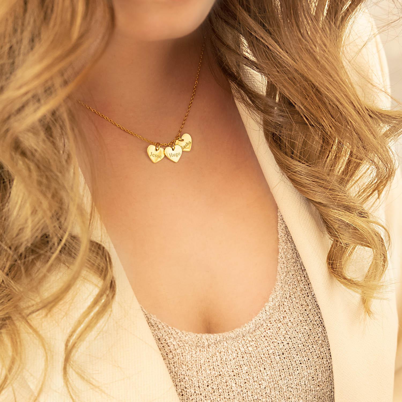 vrouw draagt gouden hartjes ketting met gravering