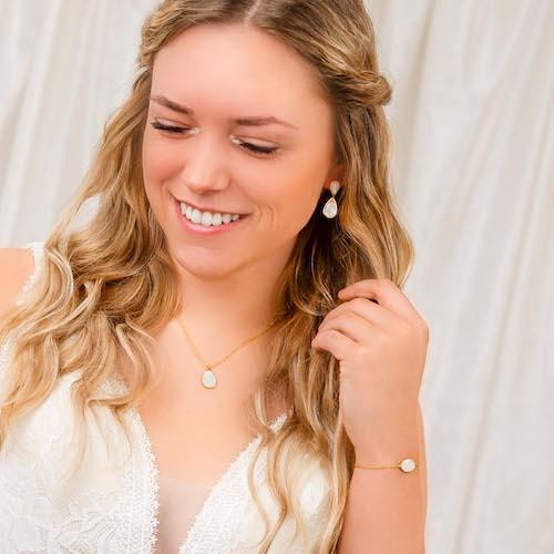 vrouw draagt gouden sieradenset met parelmoer
