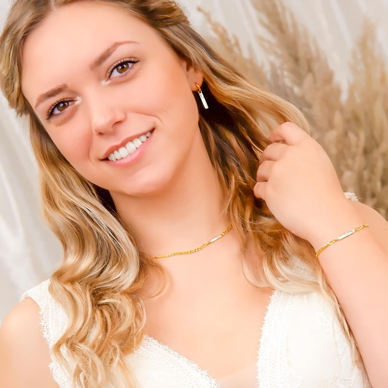 bruid draagt gouden sieradenset met parelmoer