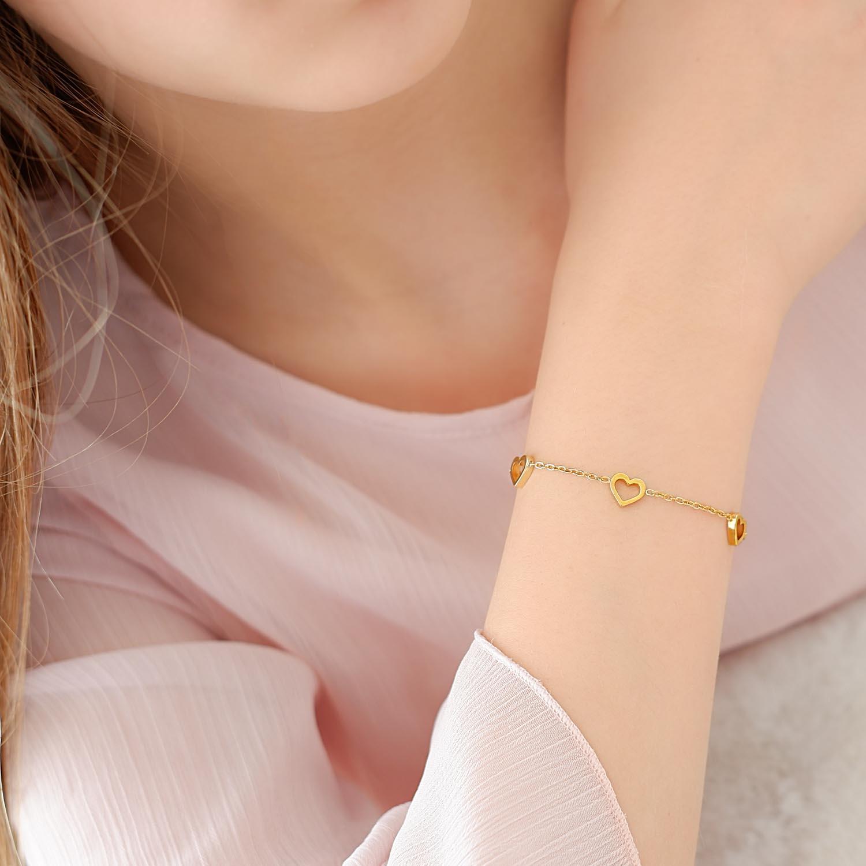 meisje draagt gouden armbandje met hartjes