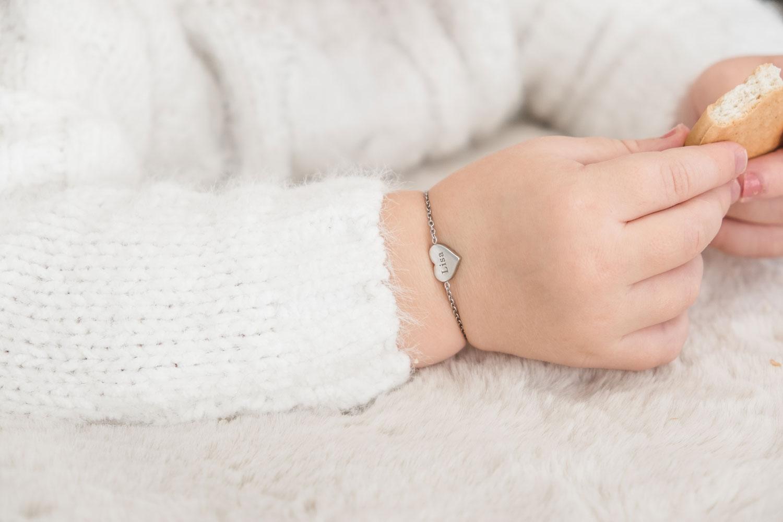 baby draagt zilveren hartjes armbandje met naam