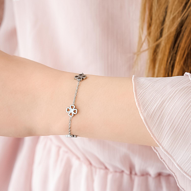 meisje draagt zilveren armbandje met klavertjes