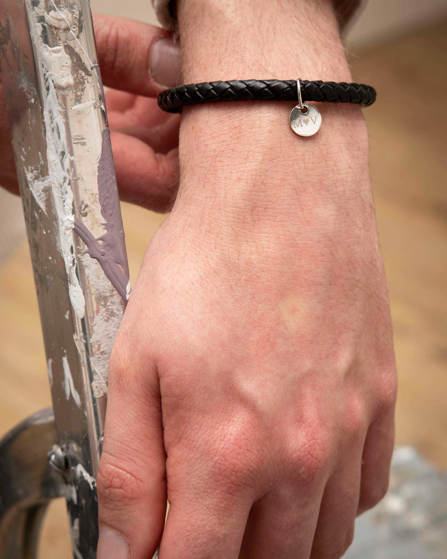 man draagt zwarte armband met graveerbaar muntje